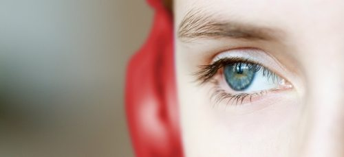 Öga och skymt av röd hörlur.
