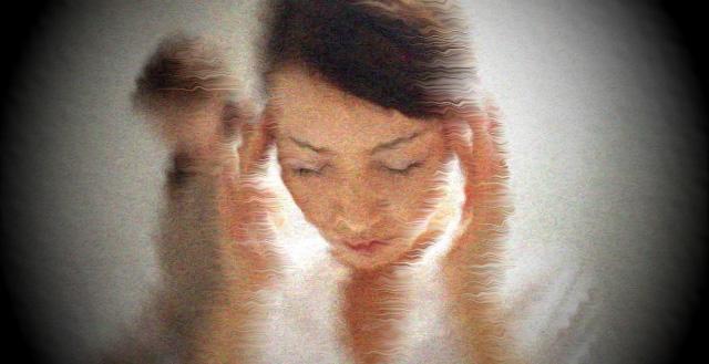 Kvinna pressar fingrarna mot tinningarna.
