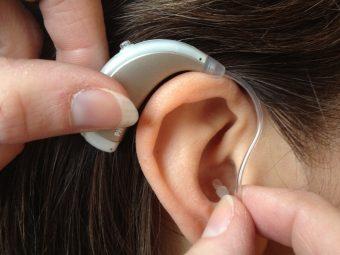 Fingrar sätter hörapparat på öra.