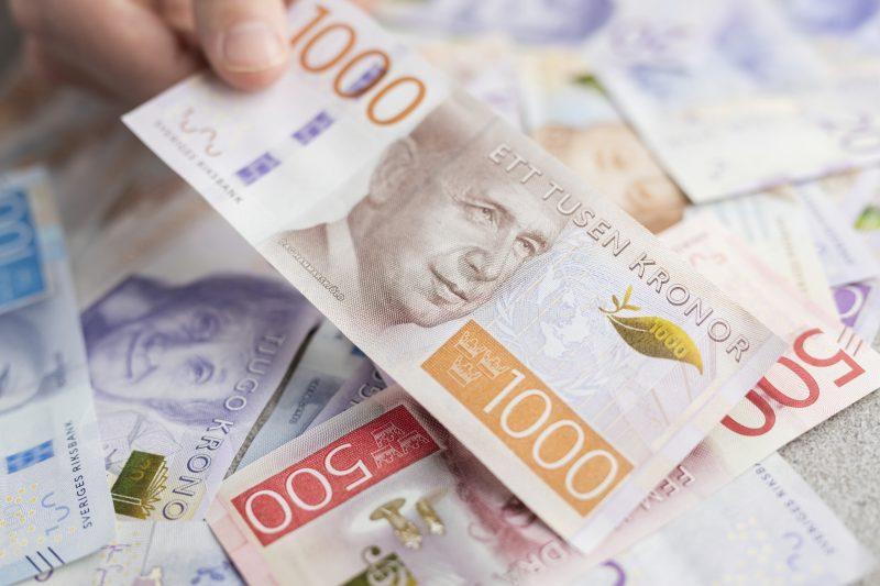 Hand som håller i svenska sedlar.