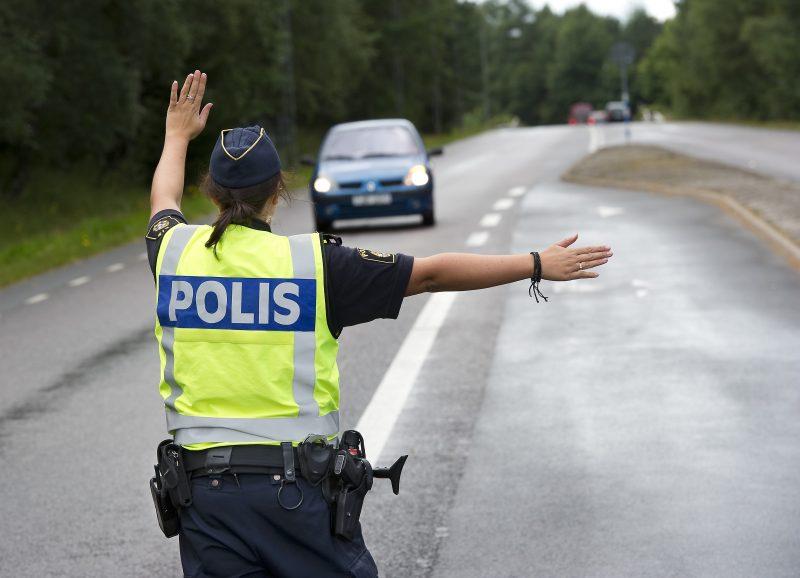 Polis som stoppar en bil på en väg.