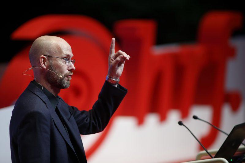 Syntolkning: Gerhard Andersson står framför stor HRF-logga, pratar och gestikulerar.