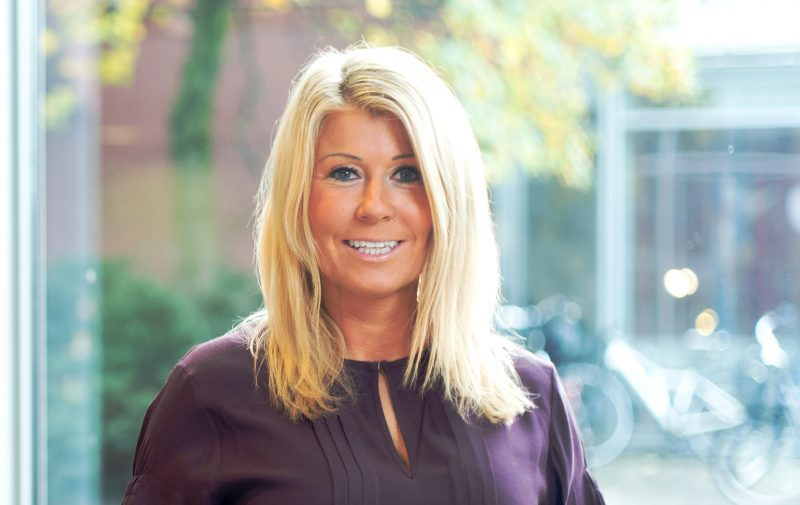 Porträtt på blond kvinna med lila blus ser in i kameran.