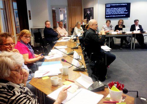 Personer sitter vid konferensbord med mikrfoner, med skrivtolkning på skärm