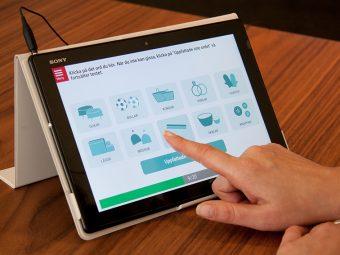 HRFs Hörseltestaren visas på en surfplatta, med en hand på person som gör testet.