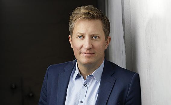 Mattias Lundekvam, porträtt där han står lutad mot en vit vägg. Halvbild.