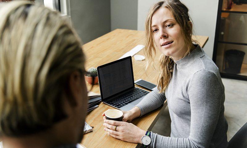 Kvinna med blont hår och i grå tröja tittar uppmärksamt på man med bakhuvudet mot kameran.
