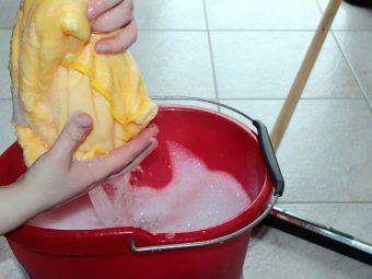 Händer vrider ur en gul trasa över en röd hink med skummande vatten.
