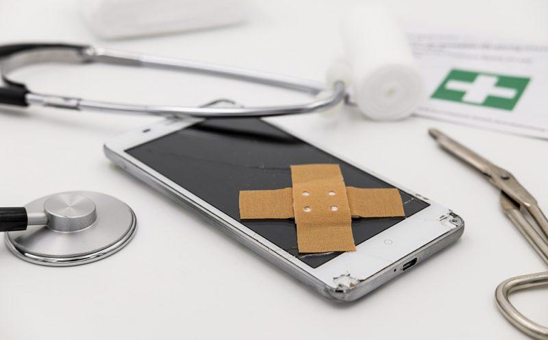 Stetosskop, plåster och gasbinda vid en mobiltelefon.