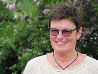 Huvudporträtt på leende kvinna med kort, mörkt hår och mörka glasögon framför syrenbuske.