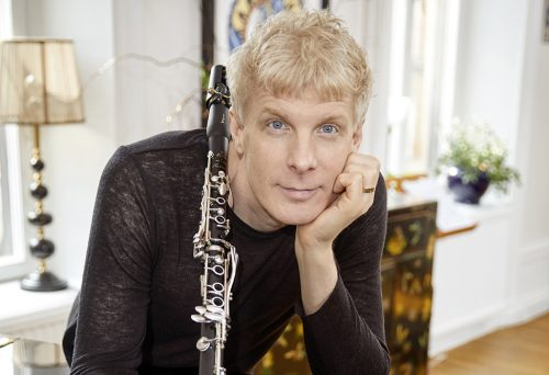 Porträtt på Martin Fröst, som ser in i kameran och håller i sin klarinett.