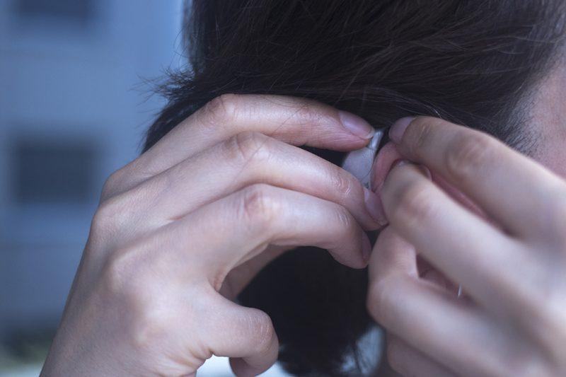 Kvinna sätter på sig hörapparat, sedd från sidan.