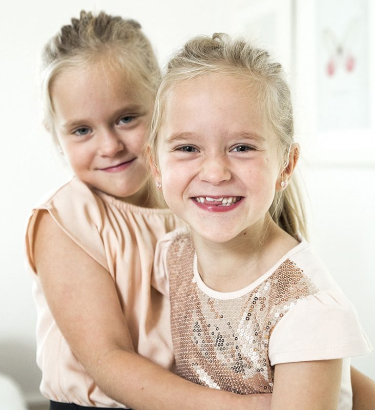 Två leende hörselskadade flickor med ljust hår.
