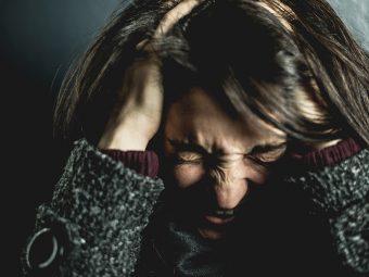 Kvinna håller hårt om huvudet och öronen.