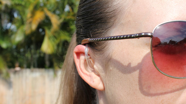 Kvinna med hörapparat och solglasögon.