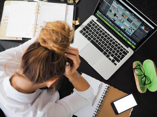 Kvinna framför laptop med huvudet i händerna, sedd uppifrån, bakifrån.