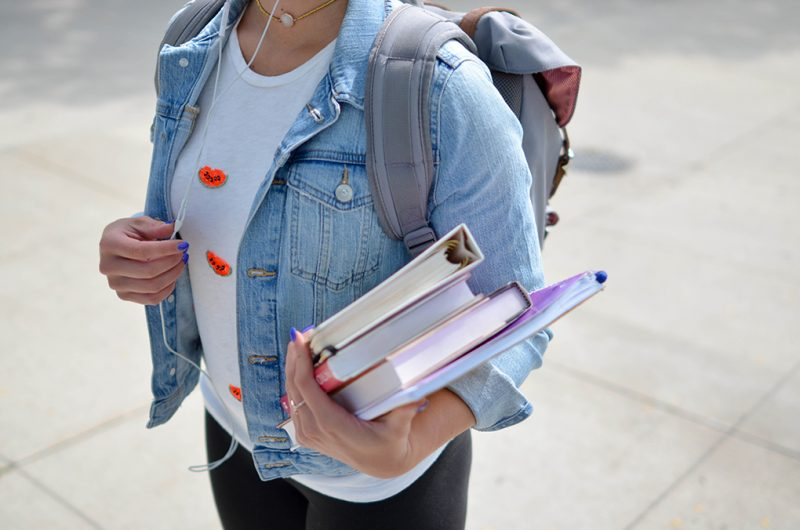 Tonårstjej med jeansjacka, böcker i handen och ryggsäck på ryggen. Huvud och ben syns inte.