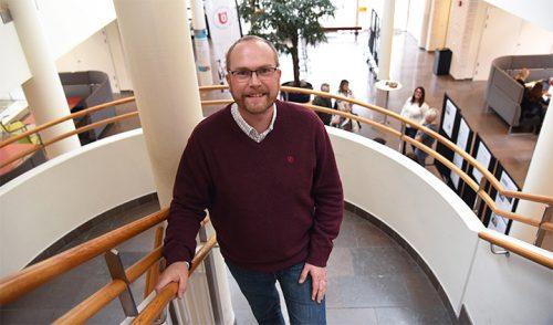 Man med skägg, glasögon och vinröd tröja står i en trappa, ler mot kameran.