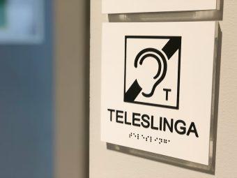 Skylt med texten TELESLINGA och internationella symbolen för teleslinga - ett öra med ett streck genom och ett T.