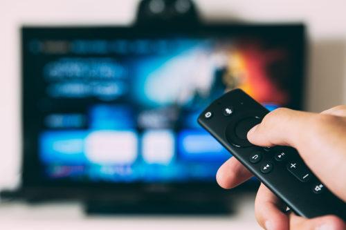 Hand håller fjärrkontroll framför suddig tv-skärm.