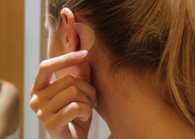 Kvinna håller plåster bakom örat