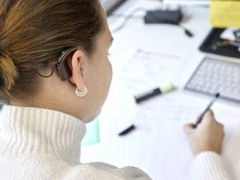 Kvinna med cochleaimplantat sedd snett bakifrån, framför skrivbord.