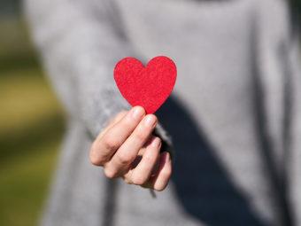 hand som håller fram rött hjärta.