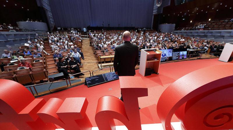 Utsikt över kongresshall full med människor, röd scen med HRFs logga i förgrunden.