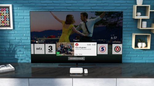 TV-skärm med kanalval över bord med vit box och fjärrkontroll.
