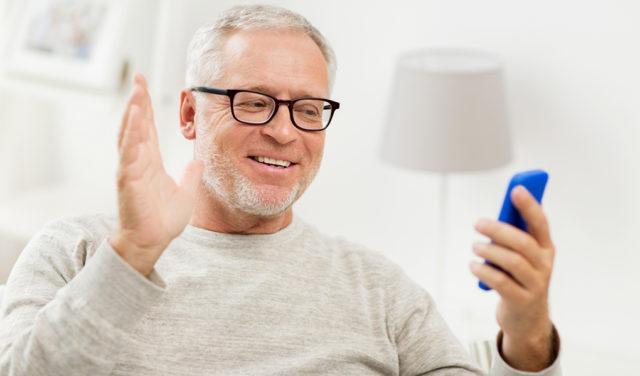 Äldre man vinkar till mobil