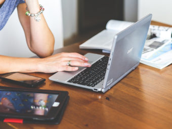 Kvinnas händer på laptop, intill surfplatta.