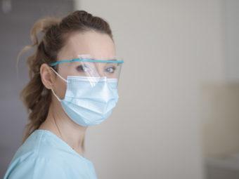 Kvinna med ansiktsmask och plastvisir.