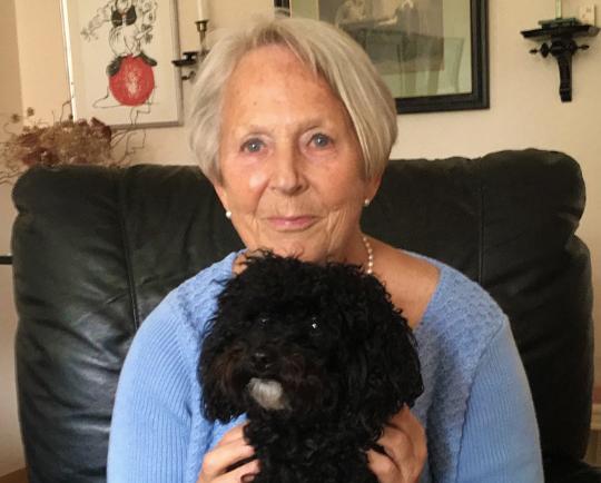 Kvinna med vitt hår, blå tröja och svart hund i knät.