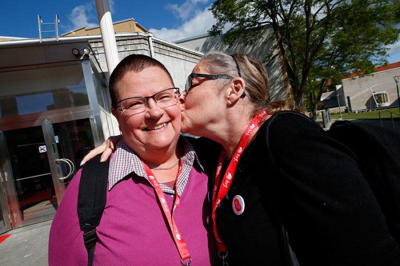 Två kvinnor med HRfs röda logoband om halsen. Den ena kvinnan ler mot kameran. Den andra pussar henne på kinden.