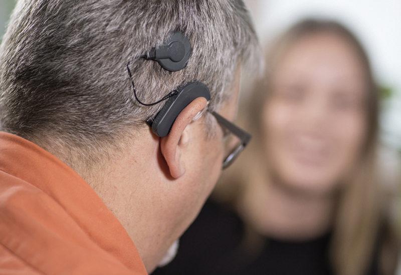 Man med cochleaimplantat och orange skjorta, sedd bakifrån. Kvinna med långt hår suddigt i bakgrunden.