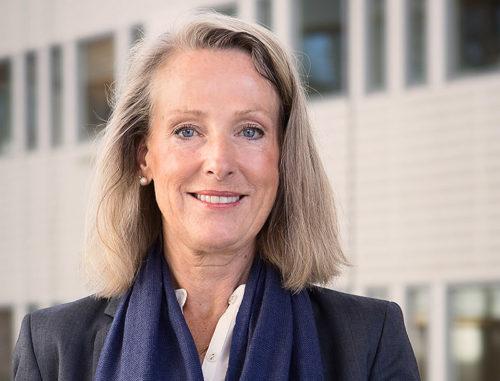 Ansiktsporträtt på leende kvinna med blondt, halvlångt hår, vit blus och mörkblå kavaj.