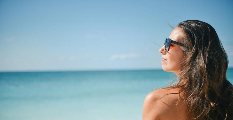Solbrun kvinna med långt hår och solglasögon i profilframför hav. och strand.