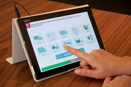 Finger pekar på ikoner på en surfplatta med Hörseltestaren.