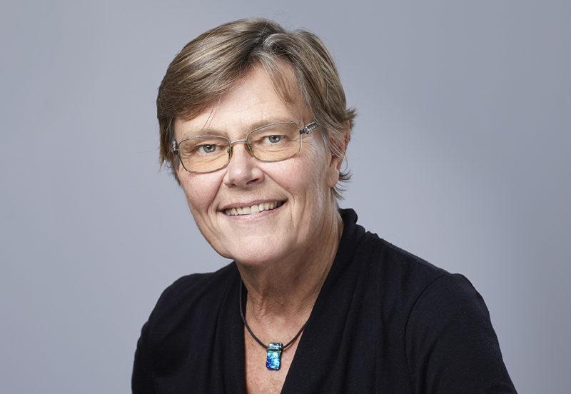 Porträtt på kortklippt kvinna med glasögon. och svart tröja.