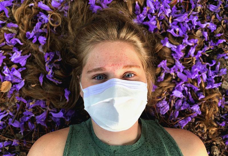 Kvinna med munskydd. Huvudet vilar på bädd med blå blommor.