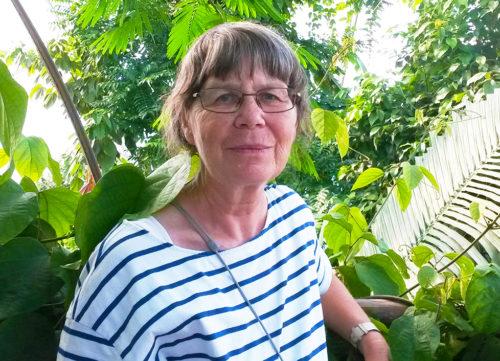 Kvinna med grått hår, glasögon och blå-vit-randig tröja står framför gröna blad.