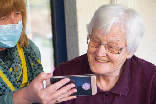 Äldre kvinna tittar på mobil som hålls fram av personal med munskydd.