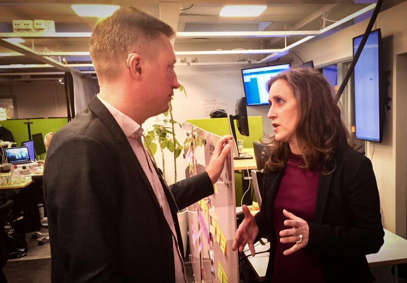 En man och en kvinna i märka kavajer står med en redaktionslokal med skärmar och skrivbord i bakgrunden. De står vända mot varandra och pratar och gestikulerar.