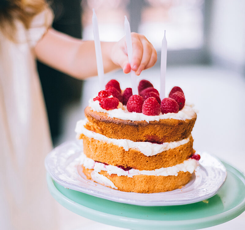 Tårta med hallon och ljus som tänds av ett barns hand.