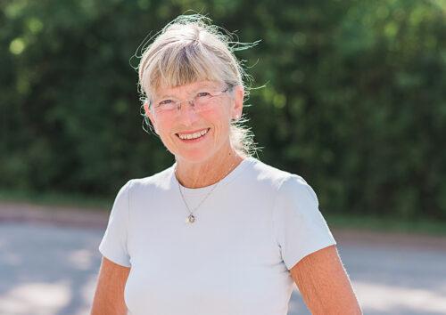 Leende kvinna i vit t-shirt och glasögon.