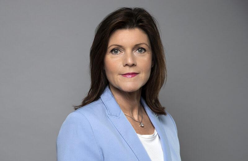 Porträtt på arbetsmarknadsminister Eva Nordmark med halvlångt mörkt hår, ljusblå kavaj och vit t-hirt.