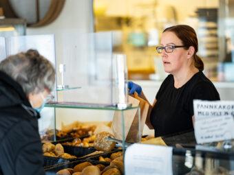 Kvinna med märkt hår och glasögon bakom disk tittar koncentrerat på äldre kvinna med munskydd.