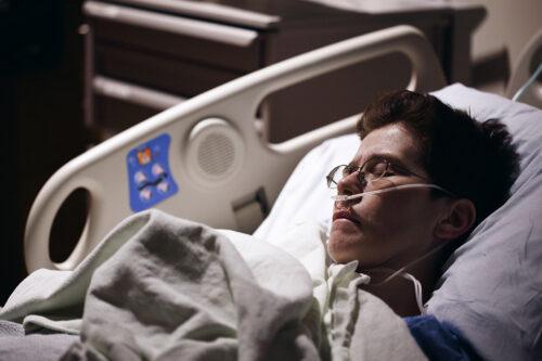 Kvinna med syrgasslang i näsan ligger i sjukhussäng.