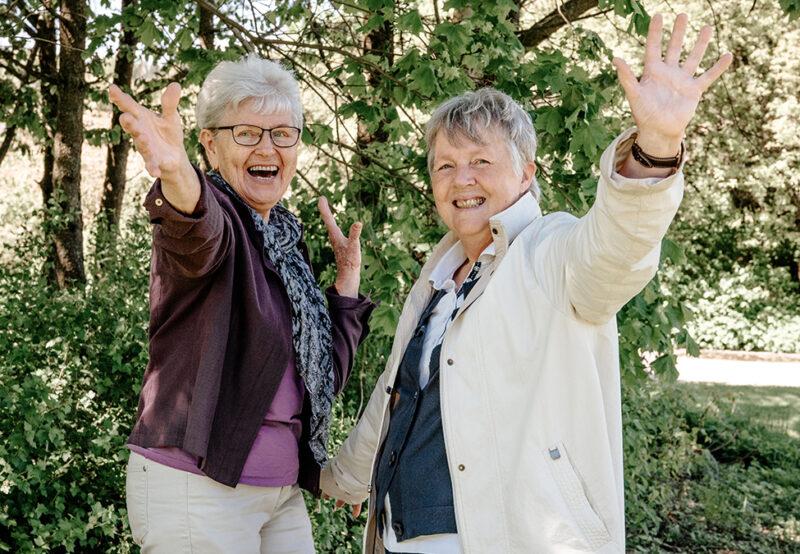 Två glada kvinnor i det gröna vinkar glatt mot kameran.