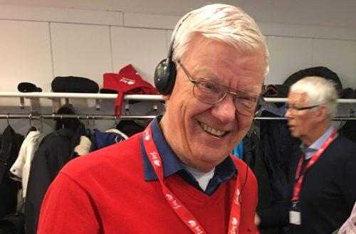 Leende man med vitt hår, glasögon, röd tröja, som bär hörlurar och ett HRF-logoband om halsen.